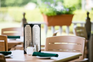 menu, salt, pepper, sugar caddy, bread plates and silverware set on outside tan deck table