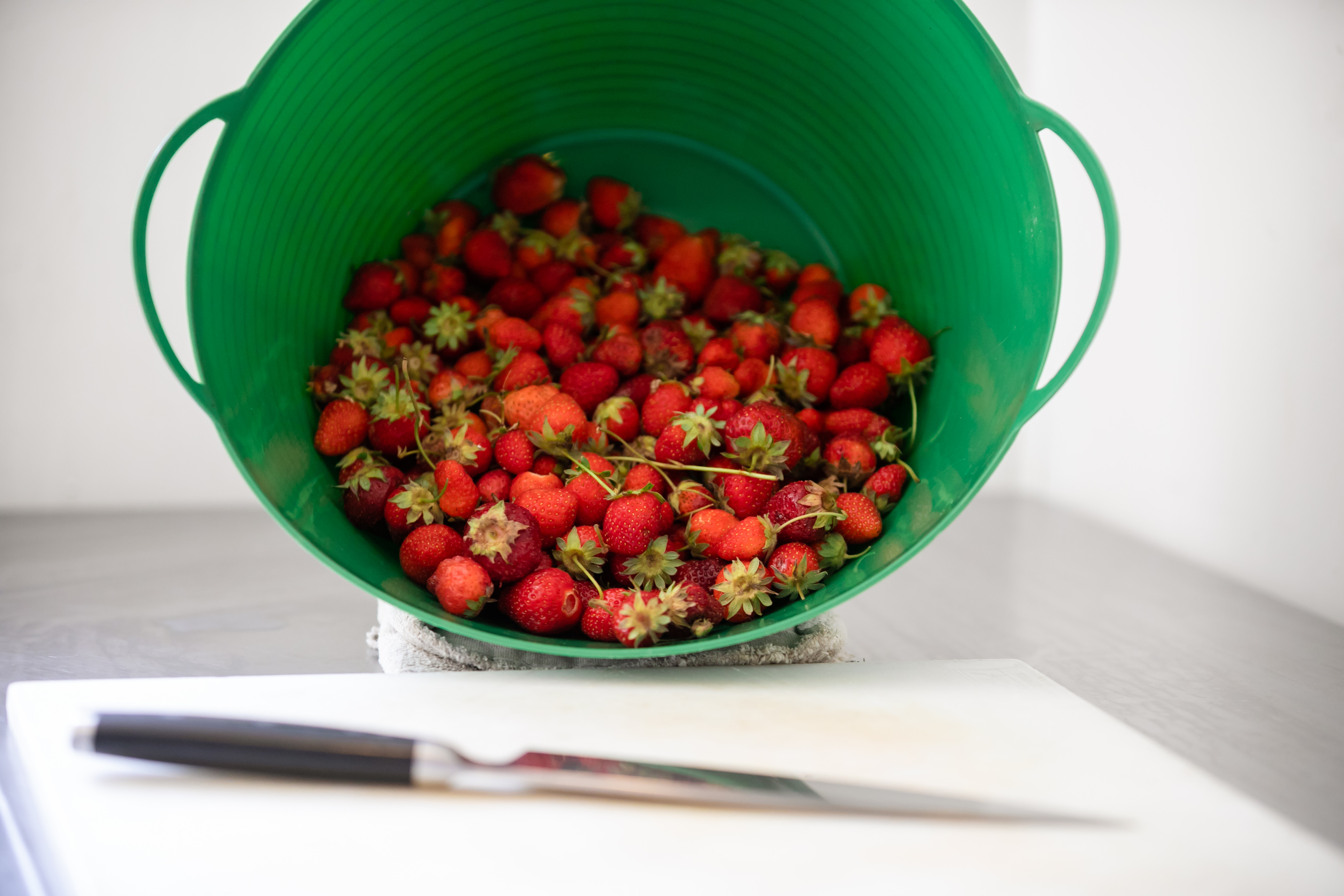 strawberries in a green plastic bucket next to a white cutting board and knife