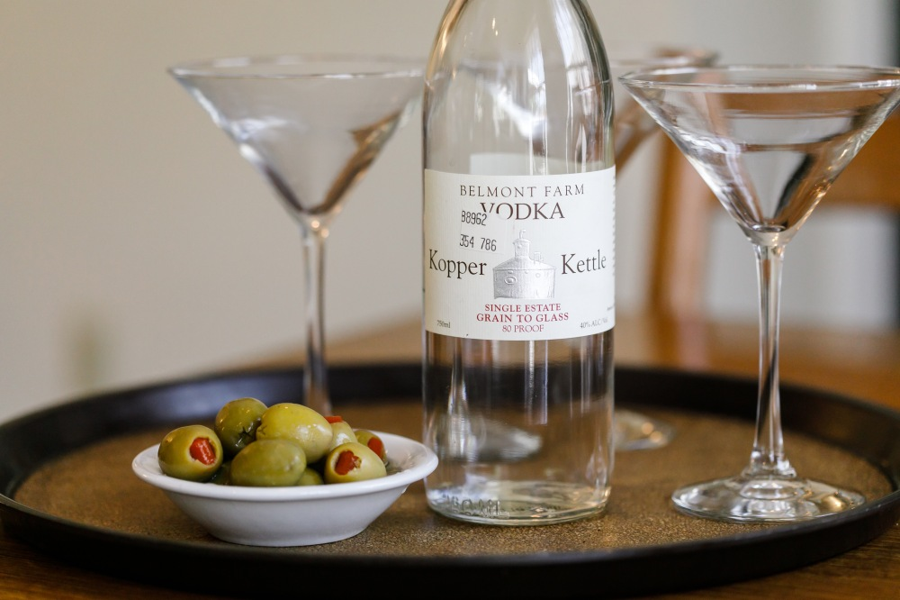 Bottle of Kopper Kettle vodka, three martini glasses and dish of olives on tray