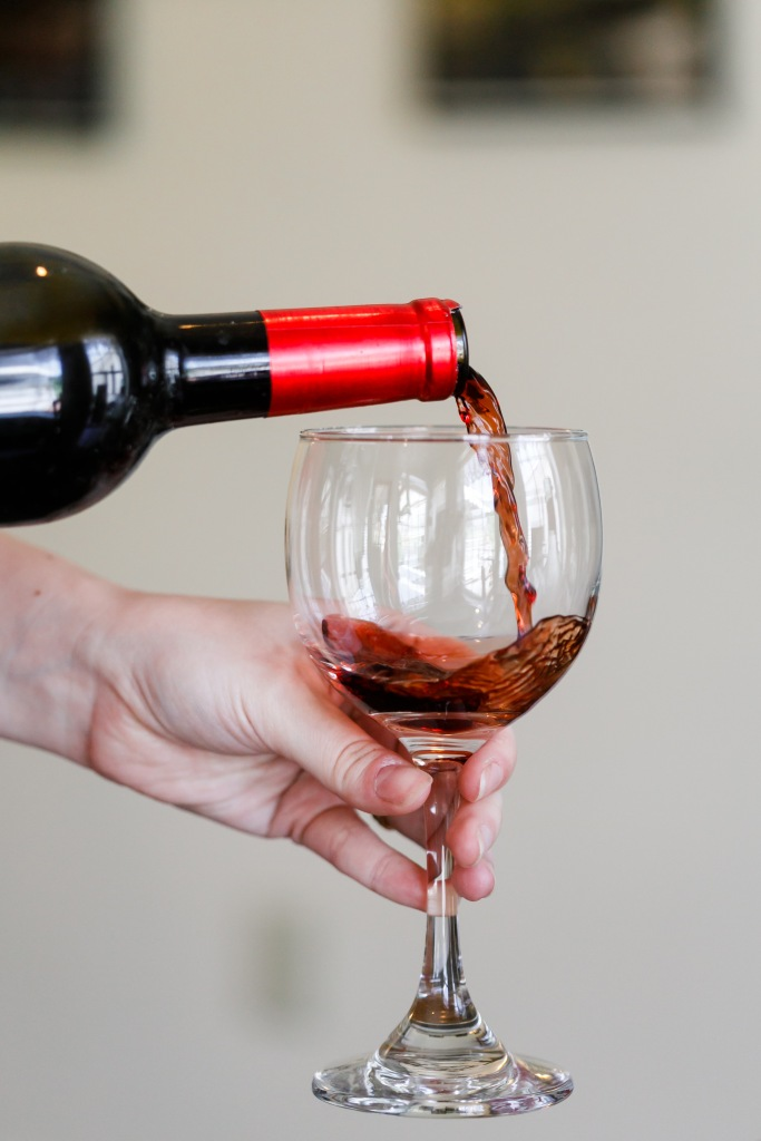 pouring bottle of red wine into a glass